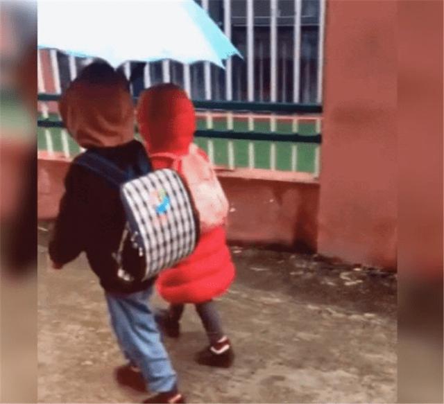 6岁的弟弟为女孩撑伞,4岁的弟弟浑身湿