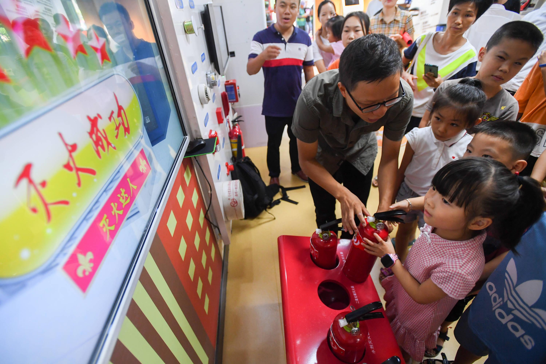 8月18日,在长沙市长沙县星沙街道消防安全科普教育馆,小朋友在体验模拟灭火器灭火.