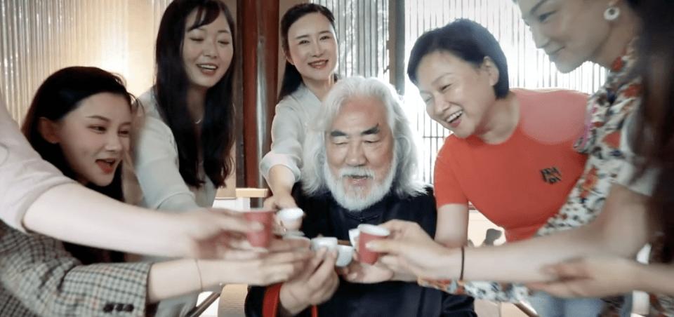 70岁张纪中生日排场大,被7位年轻美女围绕,手抱一对儿子像爷孙